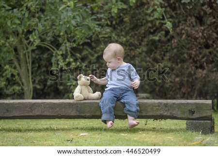 little boy with teddy bear seated on a balm in the garden - stock photo