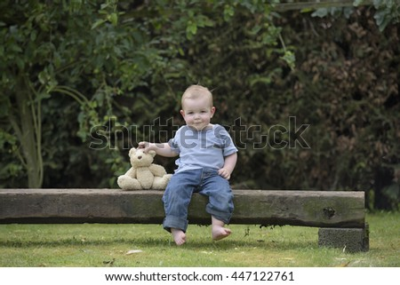 little boy with teddy bear seated on a balm in the garden
