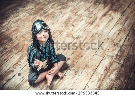 Little boy with the airplane on the floor - stock photo