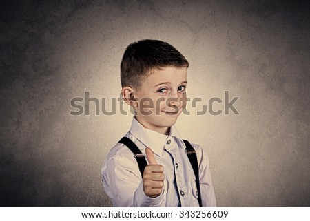 Little boy with thumb up gesture isolated over grey background.Portrait of confident happy little boy showing thumbs up gesture wearing costume  isolated over grey background.Funny,happiness. - stock photo