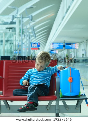 little boy with touch pad waiting in the airport - stock photo