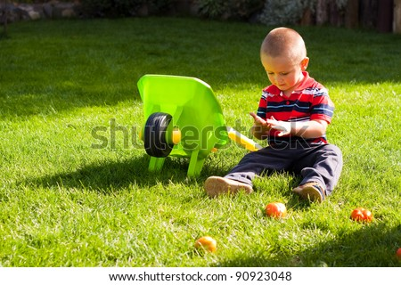Little boy with toy barrow playing in the gardening. - stock photo