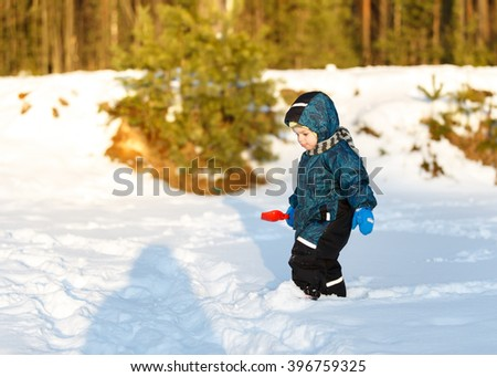 Little boy with toy scoop looking at shadow on snow - stock photo