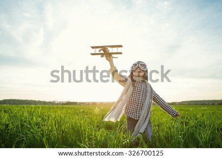 Little boy with wooden airplane in the field - stock photo