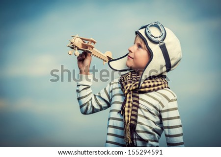 Little boy with wooden plane - stock photo