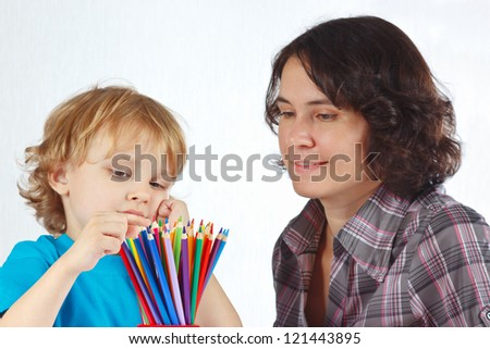 Little boy with young mother looks on color pencils on a white background - stock photo
