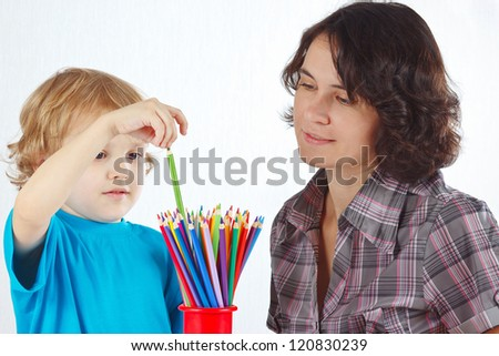 Little boy with young mother with color pencils on a white background - stock photo