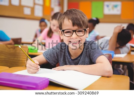 Little boy working at his desk in class at the elementary school - stock photo