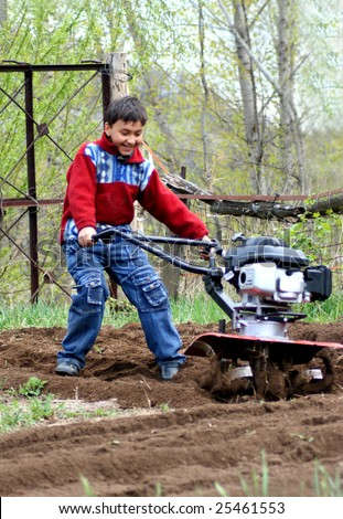 little boy working in garden with cultivator - stock photo