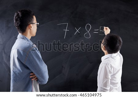 Little boy writes the answer of multiplication formula on the chalkboard with his teacher in the class