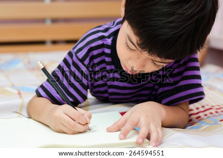 Little boy writing diary in the bed - stock photo