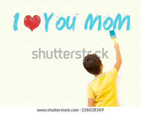 """Little boy writing """"I Love you mom"""" with painting brush on wall background  - stock photo"""