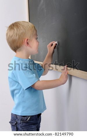 little boy writing on a blackboard - stock photo