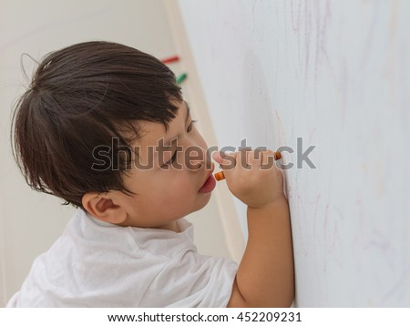 little boy writing  on wall background