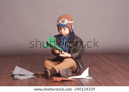 Little boy 4-5 year old playing with paper planes in room. Wearing stylish leather jacket and knitted pilot hat over gray.  - stock photo