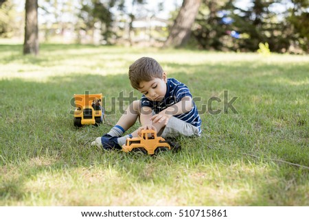Little boy, 3-4 years, playing with toys cars and trucks in the field