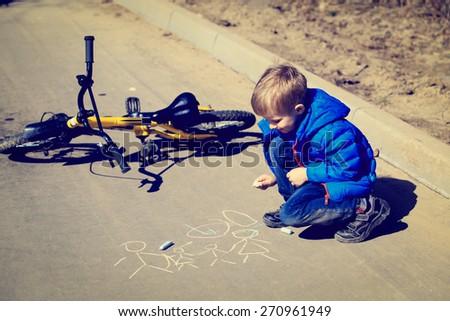 little boyl drawing family with chalk on asphalt - stock photo