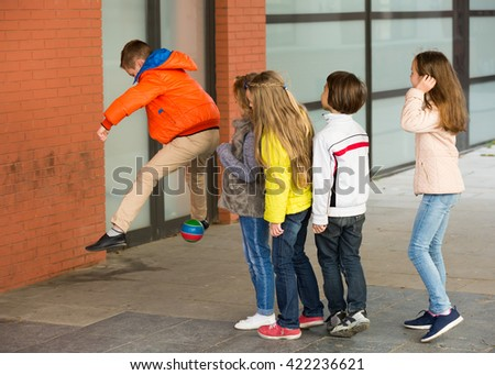 Little boys and girls hopping with ball in city street