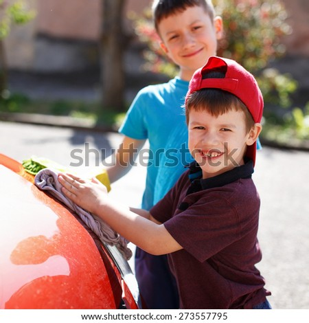 Little boys cleaning spotlight, family car wash - stock photo