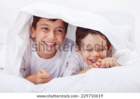 Little boys giggling together - having fun under the quilt - stock photo