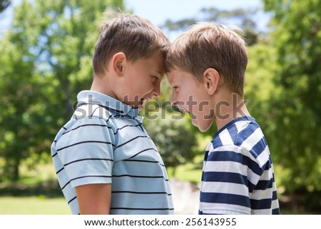Little boys having a fight on a sunny day - stock photo