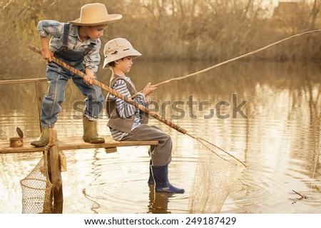 Little boys is fishing at sunset on the lake - stock photo