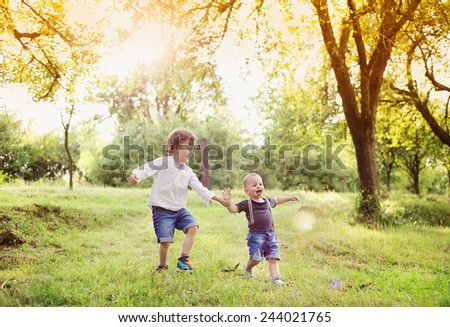 Little boys playing and having fun outside in a park - stock photo
