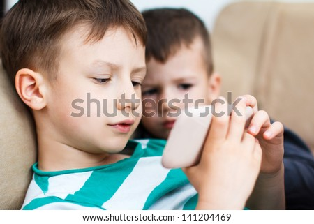 Little boys playing on smartphone, indoor - stock photo