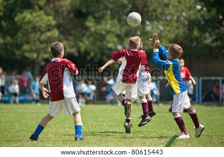 Little Boys playing soccer on the sports field - stock photo