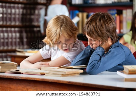 Little boys reading book together while sitting at table in library with classmates in background - stock photo
