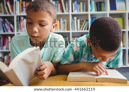 Little boys reading books in the library