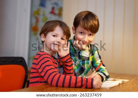 Little boys study together at desk, two person - stock photo