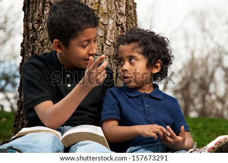 Little Boys Studying the Bible Outdoors - stock photo