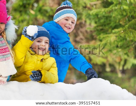 Little boys throw snowballs in the winter park - stock photo