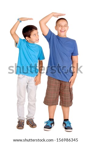 little boys trying to be taller isolated in white - stock photo