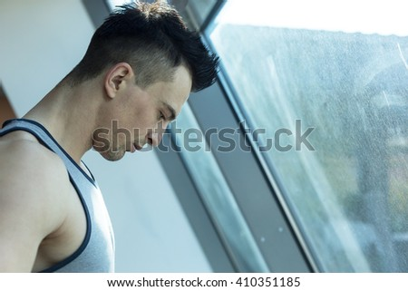 Little break. Handsome young men in sportswear at gym - stock photo