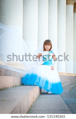 Little bride. A girl in a lush white and blue wedding dress and veil.