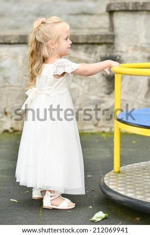 Little Bridesmaid playing in playground - stock photo