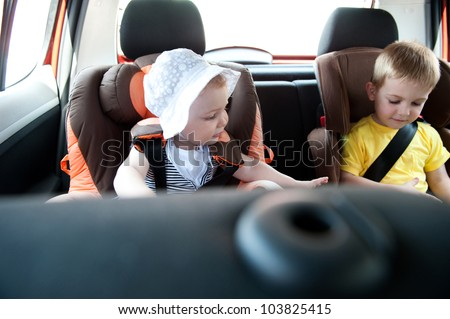 Little brother and his baby sister traveling in baby car seats - stock photo