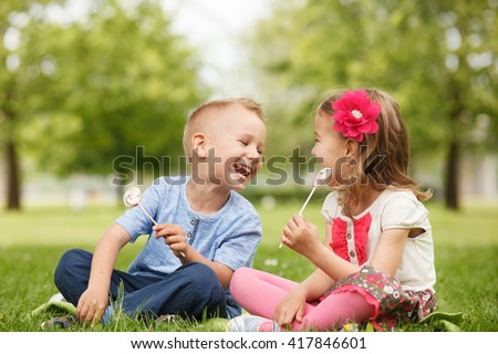 Little brother and sister enjoy lollipops and having fun in the park - stock photo