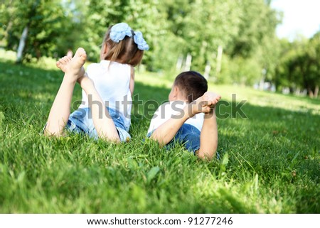 Little brother and sister lying on the grass together in summer park - stock photo
