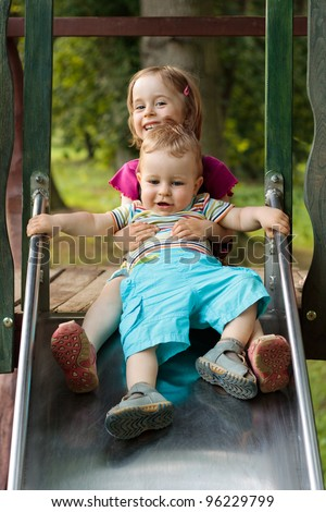 Little brother and sister playing on the slide on the playground - stock photo