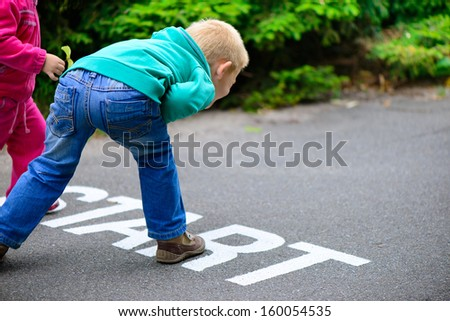 Little brother and sister running on footpath - stock photo
