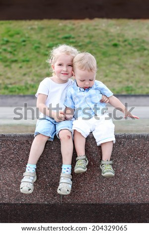 little brother and sister sitting hugging outdoors - stock photo