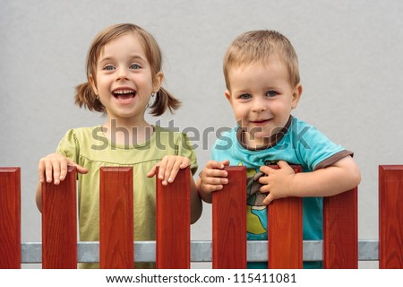 Little brother and sister smiling behind the wooden fence - stock photo