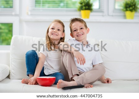 Little brother and sister watching tv on couch - stock photo