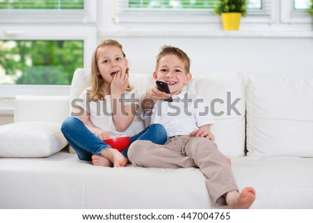 Little brother and sister watching tv on couch
