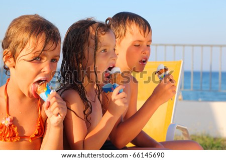little brother and two sisters in swimsuits on beach eating ice cream after bath. focus on girl in middle - stock photo