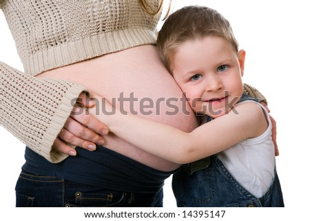 Little brother. Cute small boy talking with his pregnant mother. Studio shot isolated on white background. - stock photo