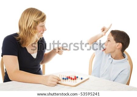 Little brother driving his teenage sister crazy while they play a board game.  Isolated on white. - stock photo